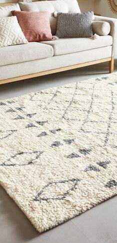 Salon aux tonalités claires mis en valeur un grand tapis berbère. Les détails en bois permettent de réchauffer la pièce et de donner cet aspect cosy.