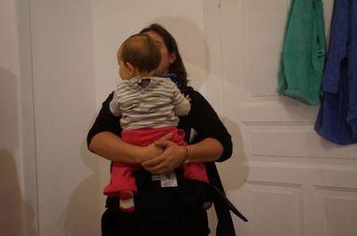 Ensuite, on prend l'enfant contre soi puis on referme les côtés. Si on a la trouille de le faire tomber, on peut clipser un côté, placer l'enfant et clipser l'autre côté.