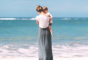 Mama mit Kind auf Arm am Meer