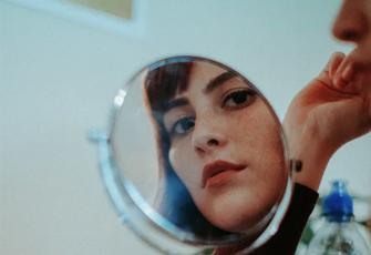 Frau schaut in Spiegel