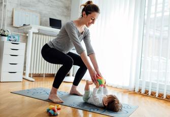 Frau macht Gymnastik mit Kind