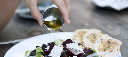 Olivenöl über Salat gießen