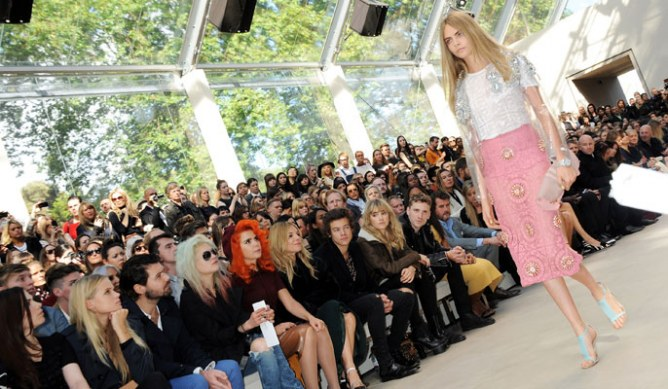 Harry Styles watches Cara Delevingne model for Burberry