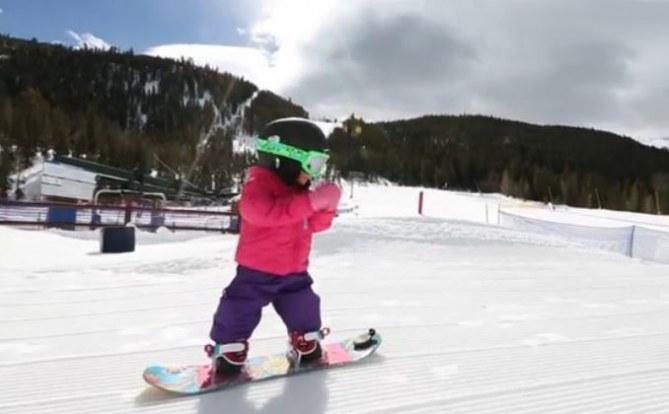 Un bébé qui fait du snowboard