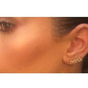 Kim présente ses boucles d'oreille au nom de North