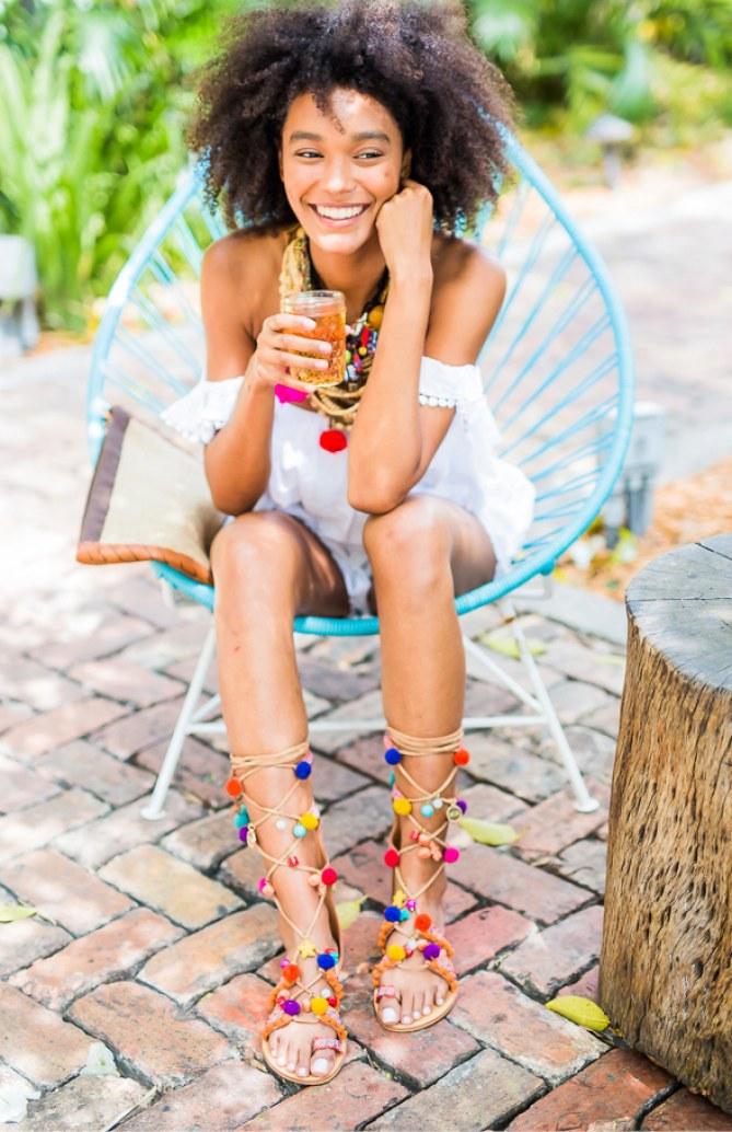 Perfekte Kombi: Ein weißes Sommerkleid und bunte Pom Pom Sandalen