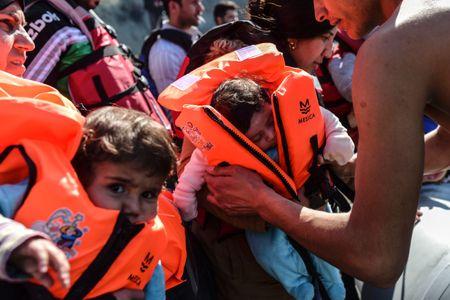 Des enfants réfugiés montant à bord d'un bateau