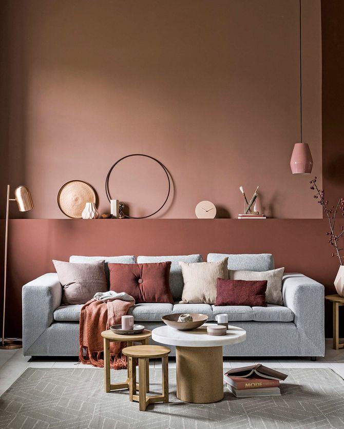 Un canapé gris avec un mur terracotta
